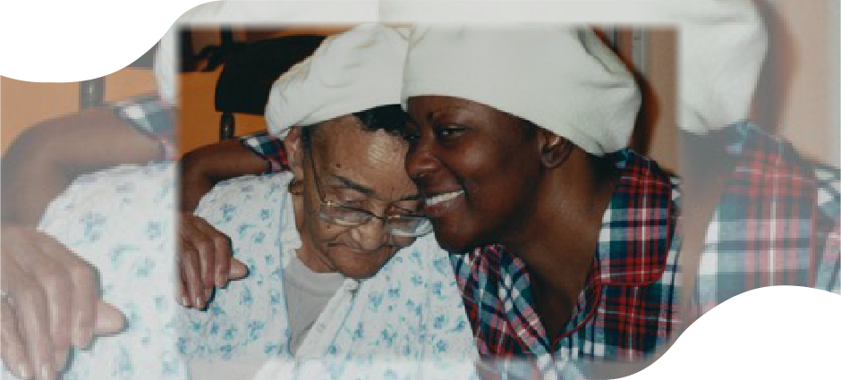 An elderly with her granddaughter and caregiver doing a thumbs up sign